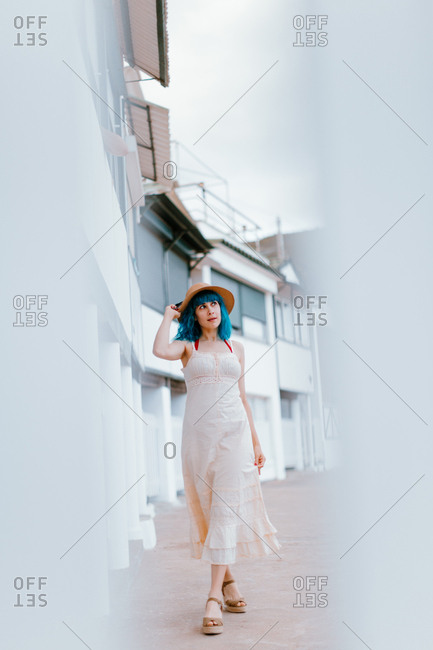 Relaxed woman with blue hair in hat and sundress strolling along city street at summer day