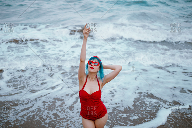 Fashionable woman with blue hair in red swimsuit enjoying water staying in foamy waves with raised hands up