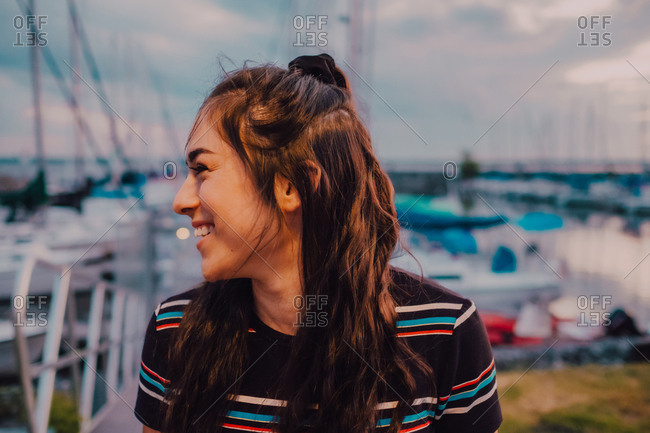 Happy young tattooed woman in dress standing on wharf filled with yachts and boats