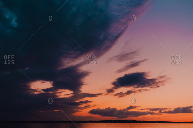 Stunning colorful sundown in warm summer evening reflecting lightly in sea surface