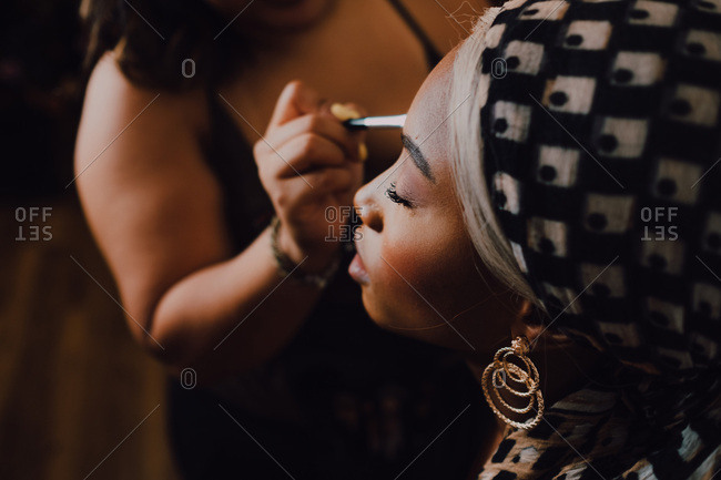 Attractive black adult female applying eye shadow from professional makeup artist in studio