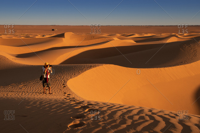 Unrecognizable traveler taking pictures of dunes while standing on sand in amazing desert
