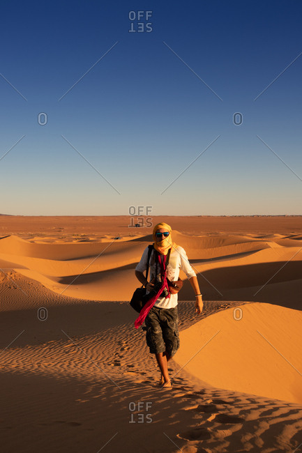 Unrecognizable tourist with outstretched arms standing against bright cloudless sundown sky in desert