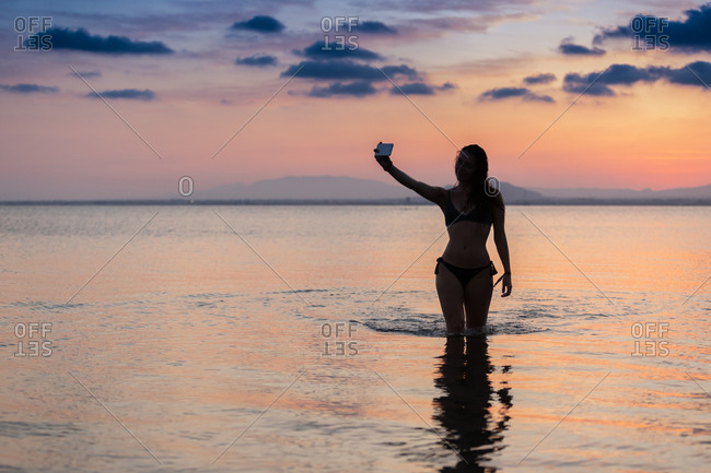 Seductive female taking selfie in water