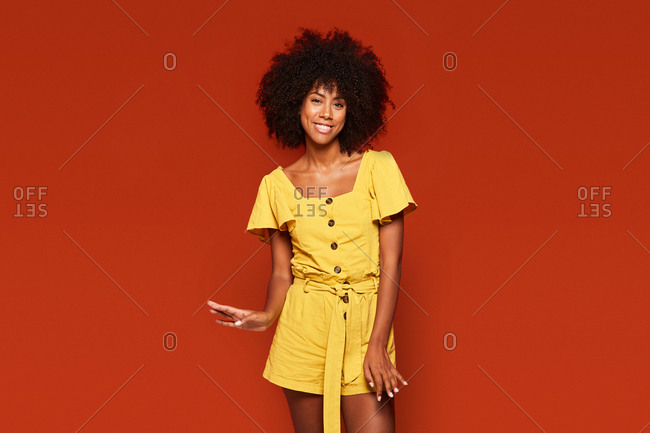 Vivid carefree african american woman in bright yellow dress standing on red background and looking at camera
