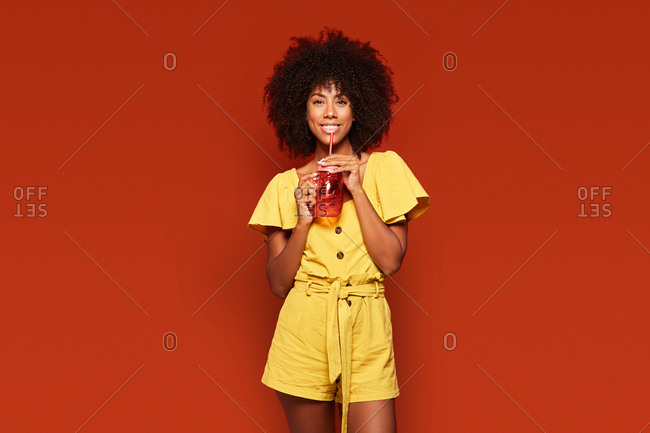Cheerful young african american lady with curly hair holding red jar with straw and enjoying beverage on red background looking at camera