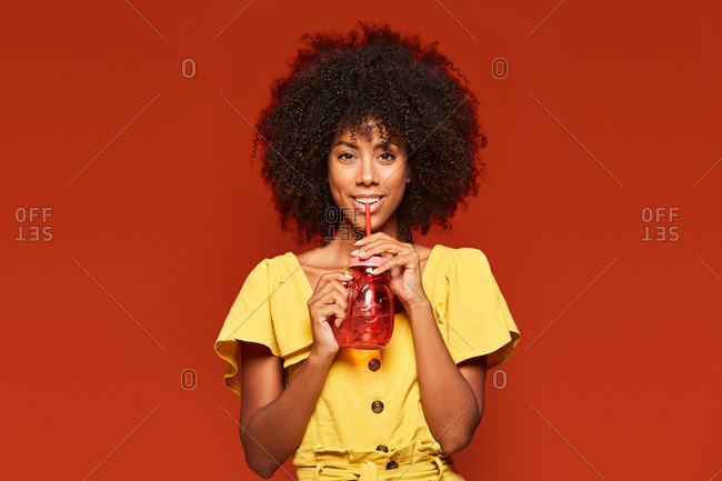 Dreamy young african american lady with curly hair holding red jar with straw and enjoying beverage on red background looking at camera
