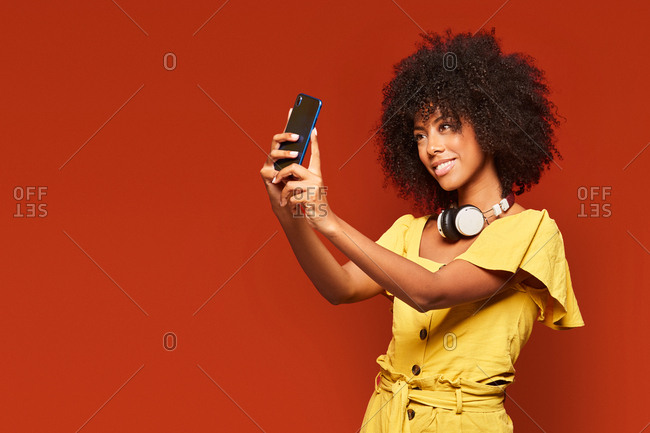 Modern happy ethnic woman with curly afro hair wearing headphones on neck and taking selfie with mobile phone on vivid red backdrop