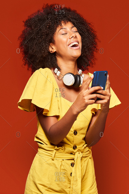 Modern happy ethnic woman with curly afro hair wearing headphones on neck and using mobile phone and laughing out loud on vivid red backdrop