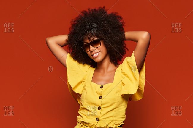 Modern young black woman with afro hairstyle holding hands behind head while smiling at camera on bright red background