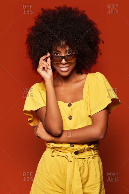 Modern young black woman with afro hairstyle posing while smiling at camera on bright red background