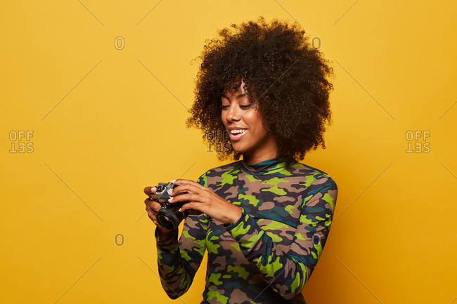 Professional cheerful female photographer with afro hairstyle reviewing pictures on stylish photo camera while standing at yellow background