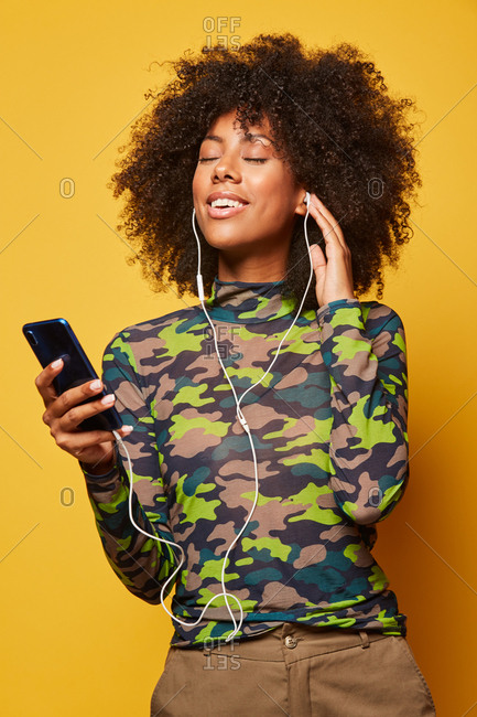 Low angle of woman listening to music in earphones while standing with closed eyes on yellow background