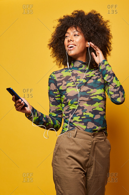 Low angle of cheerful woman listening to music in earphones while standing on yellow background