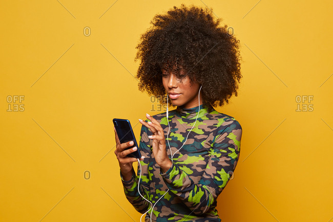 Cheerful woman listening to music in earphones while standing on yellow background