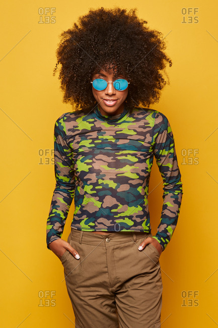 Modern young african american woman with afro hairstyle wearing camouflage shirt with sunglasses standing on yellow background posing with hands on pockets and looking at camera