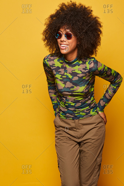 Modern young cheerful african american woman with afro hairstyle wearing camouflage shirt with sunglasses standing on yellow background and looking away