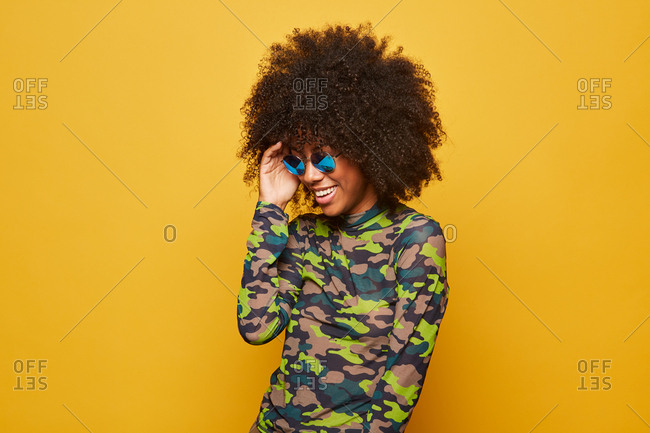 Modern young african american woman with afro hairstyle wearing camouflage shirt with sunglasses standing on yellow background and looking down