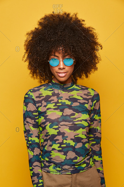 Modern young african american woman with afro hairstyle wearing camouflage shirt with sunglasses standing on yellow background and looking at camera