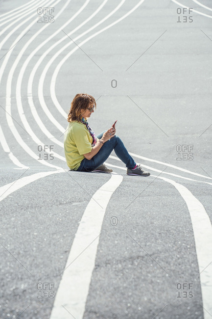 Modern relaxed woman on marked road and browsing smartphone