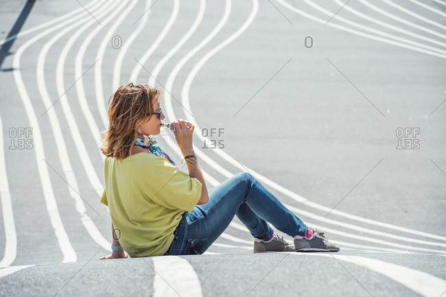 Side view of adult chilling woman in sunglasses and colorful outfit exhaling steam while sitting on twisting asphalt road