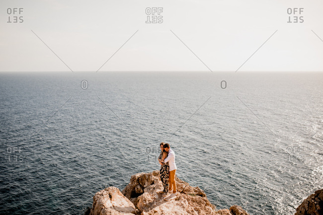 From above peaceful woman and man hugging on stone cliff above endless ocean landscape