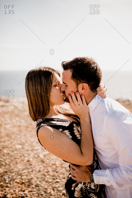 Side view of passionate woman and man kissing tenderly on nature in summer