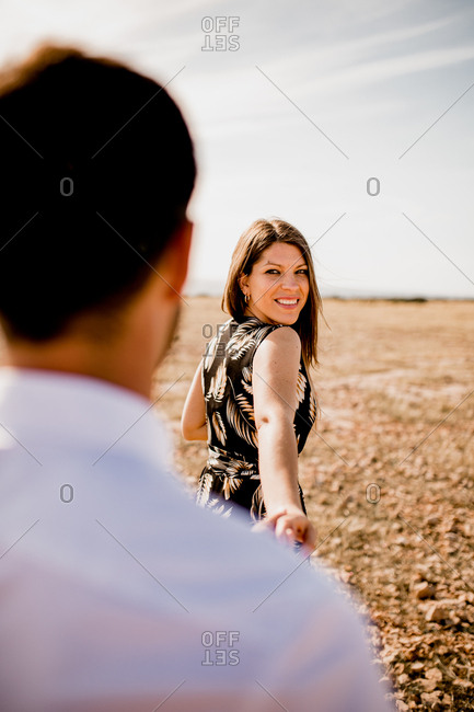 Soft focus of delighted tender couple holding hands on field in summer