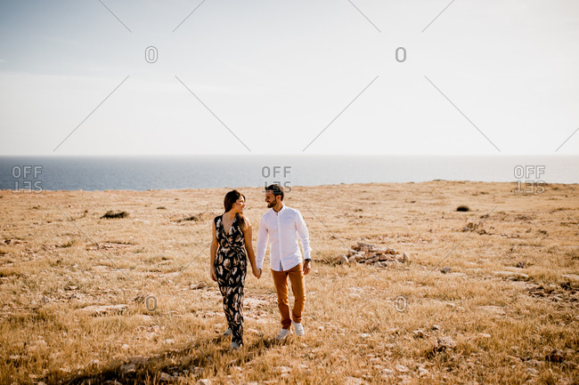 Peaceful lovers bonding on empty coastline