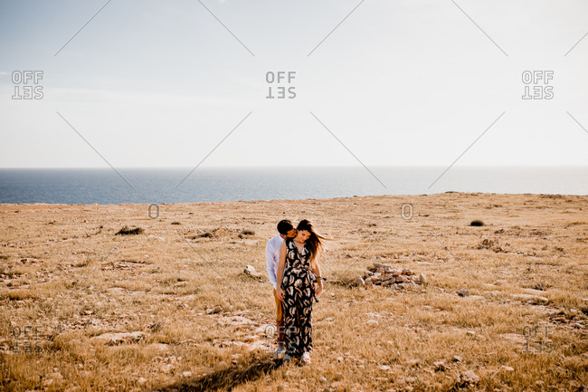 Serene tender man and woman standing close and kissing on remote golden seashore of ocean