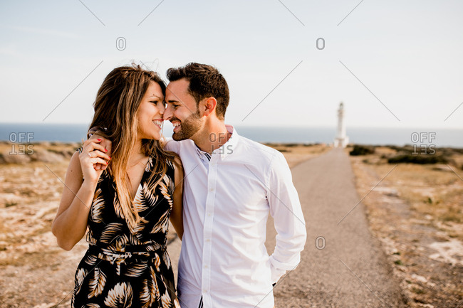 Smiling lovers cuddling on path to sea