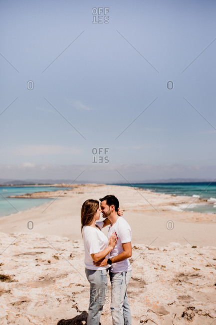Side view of affectionate man and woman in casual wear bonding on seashore in summer