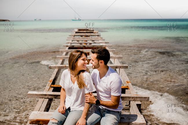Glad lovers sitting on destroyed pier on seashore