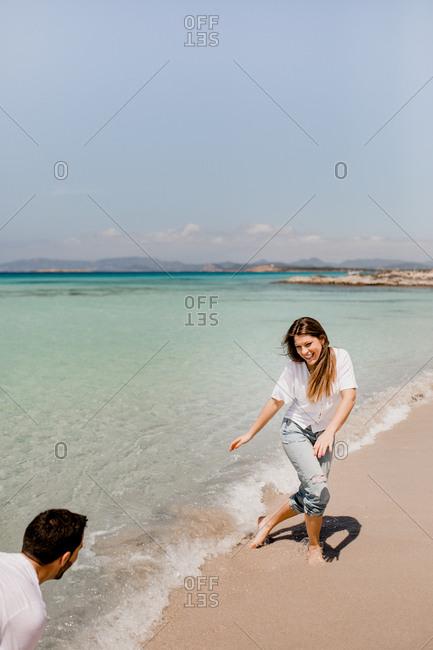 Cheerful lovers having fun on tropical coastline