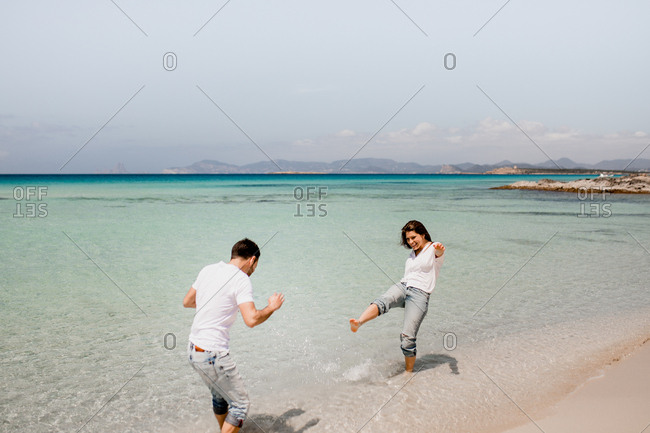 Playful man and woman in white shirts playing in shallow water of seashore in summer