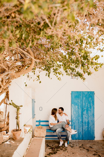 Smiling man and woman chilling on wooden bench in embrace at light patio in summer and looking at each other