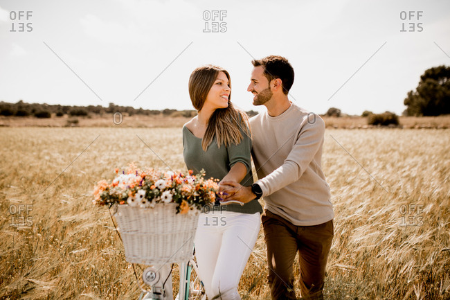 Sincere lovers posing by bicycle on rye field