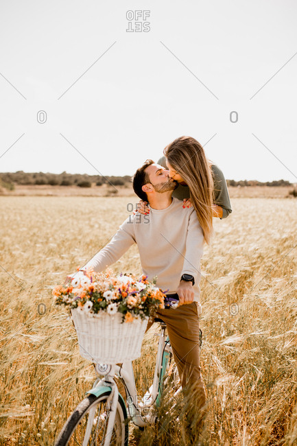 Playful lovers riding bicycle on wheat field