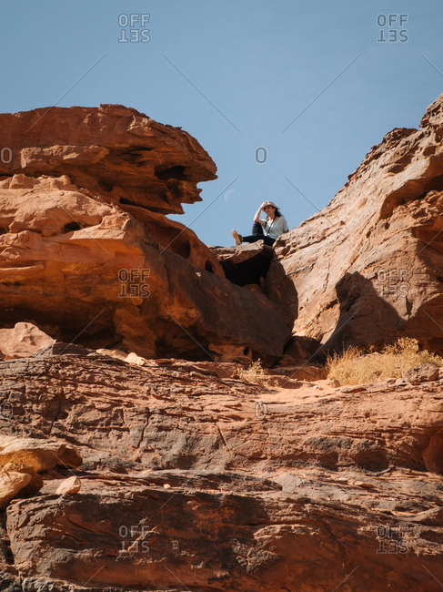From below female traveler sitting on rough rock formation against cloudless blue sky in wadi rum desert in jordan