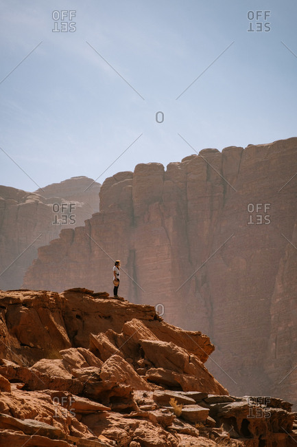 Side view of distant female traveler standing on rocky cliff against mountain ridge on sunny day in wadi rum desert