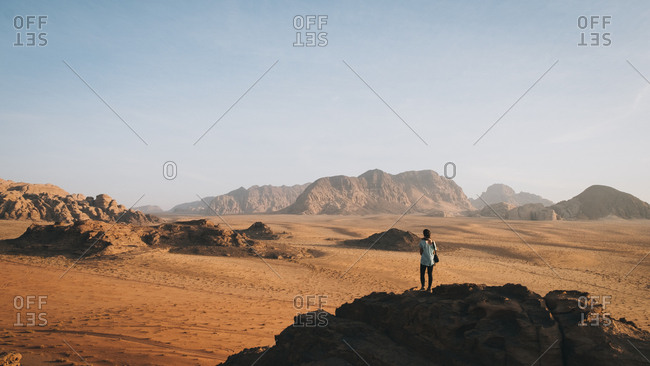 Woman stands on top of the rock looking at wadi rum