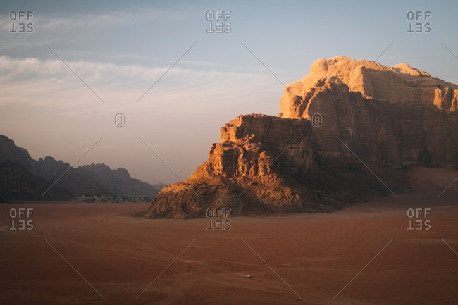 A jeep in the middle of the giant desert of wadi rum during sunset