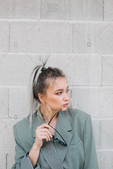 Fashion attractive woman holding sunglasses and leaning on brick grey wall looking aside