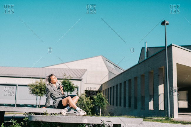 Trendy businesswoman working outside sitting on round decorative panel plates nearby building closing eyes enjoying sun in bright day