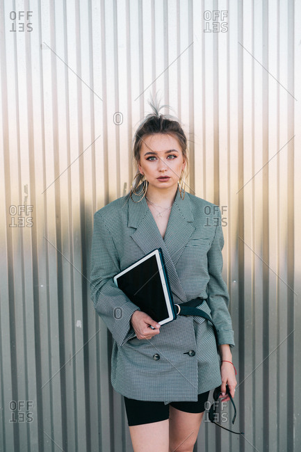 Trendy businesswoman holding tablet and sunglasses leaning metal wall and looking at camera with questioning expression