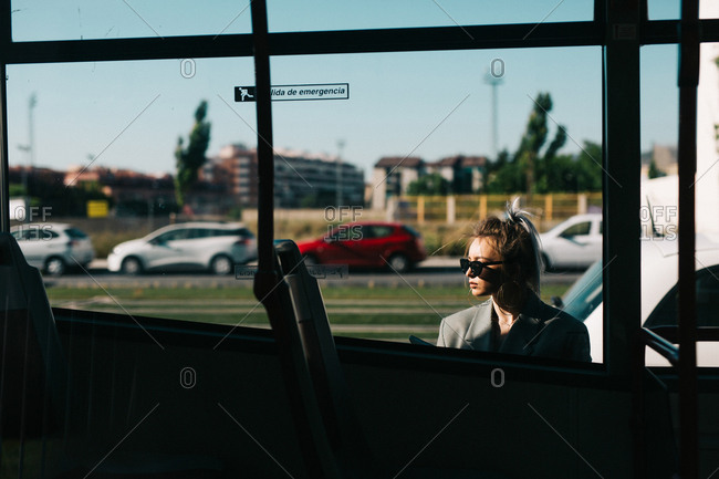Trendy businesswoman and sunglasses leaning behind bus and looking away