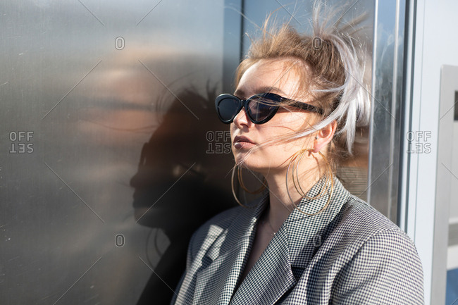 Fashion attractive woman with trendy hairstyle and sunglasses nearby dark shiny metal wall looking away