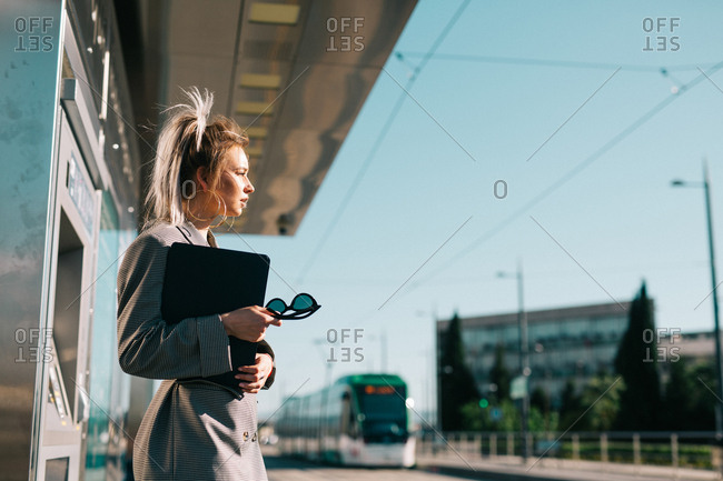 Side view of stylish trendy businesswoman waiting for train and tensely looking away at station
