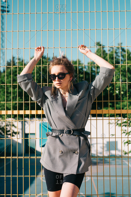 Trendy fashionable businesswoman looking at camera in sunglasses and leaning on yellow lattice in bright day on playground