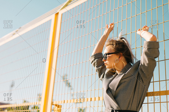 Trendy fashionable businesswoman looking away in sunglasses and leaning on yellow lattice in bright day on playground